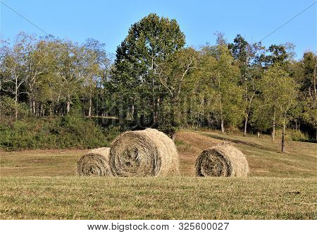 A Trio Of Hay Bales In A Field On A Farm In West Virginia.