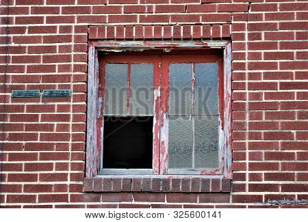 Peeling Red Paint Adorns The Broken Window On The Side Of An Old Brick Building.