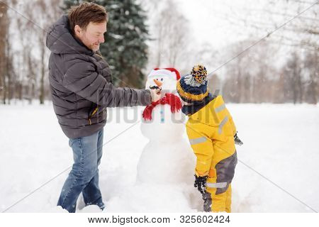 Little Boy With His Father Building Snowman In Snowy Park. Active Outdoors Leisure With Children In