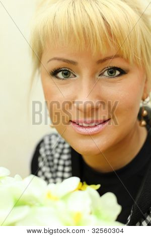 Portrait of happy beautiful blonde woman with white flowers