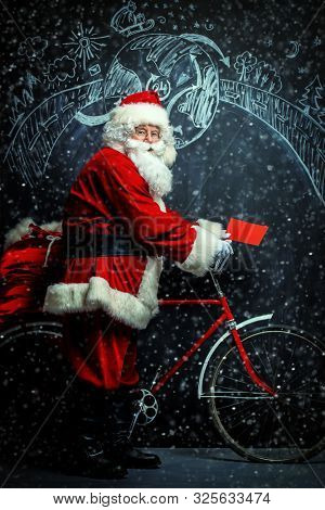 A portrait of Santa Claus with a bike and gifts. Merry Christmas and Happy New Year!