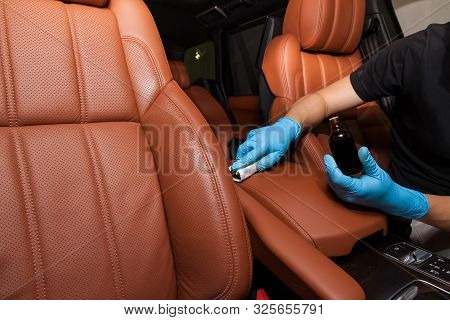 Applying A Nano-ceramic Coating On Leather Of The Car Seat Brown Upholstery By A Worker In Blue Glov