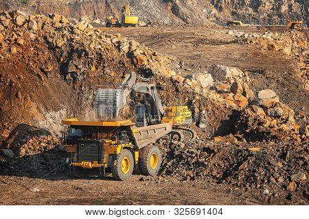 Gold Ore Mining, Loading Excavator Bucket Into Body Of Mine Truck