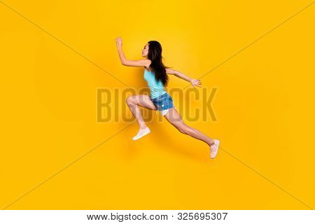 Full length body size photo of side profile sports woman in urgency running after sales and discounted goods wearing jeans denim shorts sportive sneakers isolated vibrant color background poster