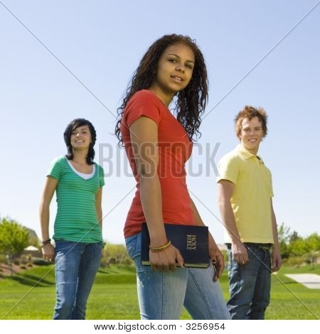 Three Teens In Park With Bible