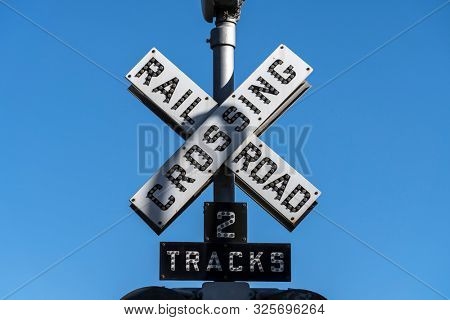 Old railroad crossing two tracks signal sign.