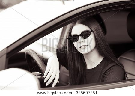 Beautiful Girl 20-24 Year Old Wearing Stylish Sun Glasses Driving Car. Looking At Camera. Auto Lady