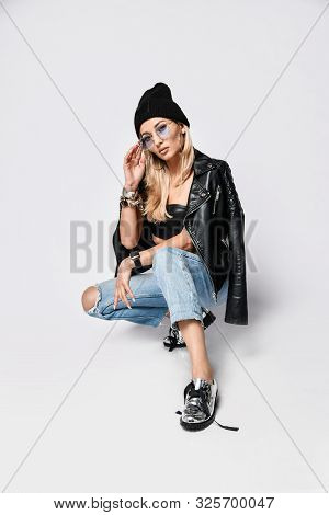 Portrait Of Punk Style Blonde Girl In Torn Jeans, Leather Top, Leather Jacket, Knitted Winter Hat An