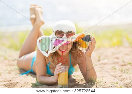 Pretty Woman 30-35 Years Old In A Blue Bikini Sunbathes On Beach Holds Juice In Her Hand. The Girl L