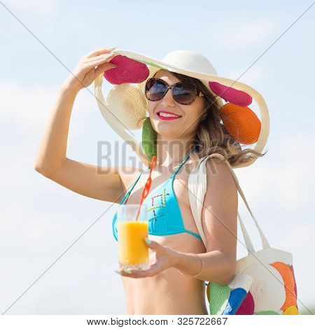 A Cute Woman Of 30-35 Years Old In Blue Bikini Walks Along The Beach Holding Juice In Her Hand A Gir
