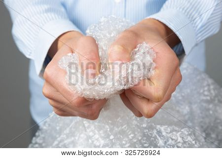 Female Hands Popping The Bubbles Of Bubble Wrap. Stress Relief, Anger Management