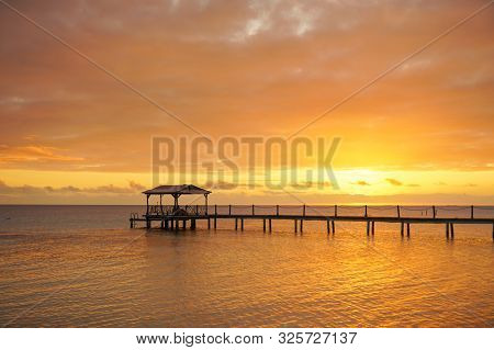 A Dock Leads Out Over A Lagoon At Sunset On The Island Of Fakarava In French Polynesia