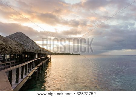 A Wooden Walkway With Thatched Roof Bungalows Leads Out Into The Lagoon On The Island Of Moorea In F