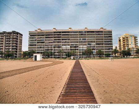 Modern Buildings Next To The Beach With A Wooden Walkway Leading To Them On A Cloudy And Rainy Day I