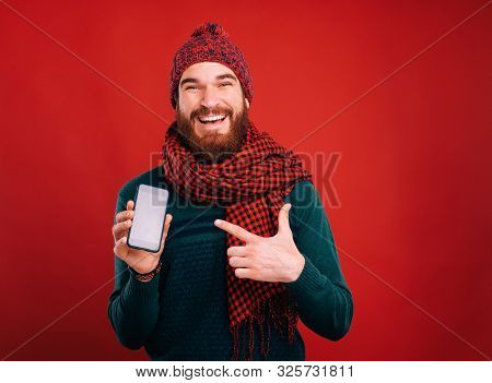 Man Poiting At His Phone Showing An Offer Or App. Holliday Season