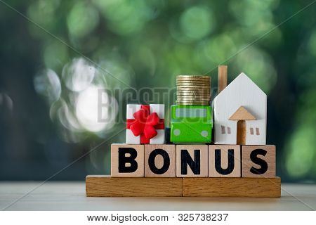 Miniature Home, Car And Money Put On Wood Block In Word Bonus. Yearly Bonus Concept. Bonus Is Motiva