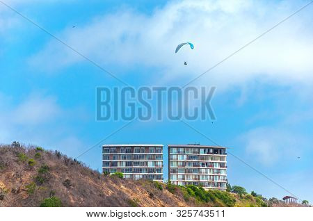 Paraglider Flying Over Buildings And Mountains At The Beach, San Pedro, Manabi Ecuador