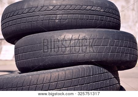 Old Worn Damaged Bald Car Tires Stacked On Top Of One Another. Recycling Concept
