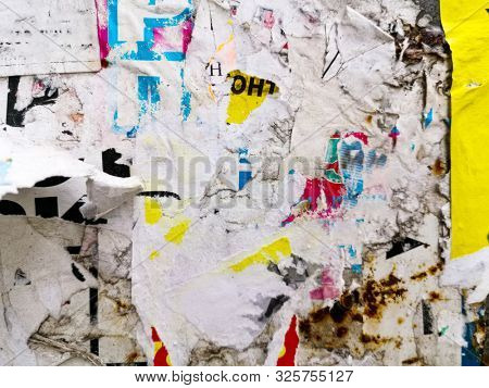 Vintage old posters sticked and torn on wall for your grunge background