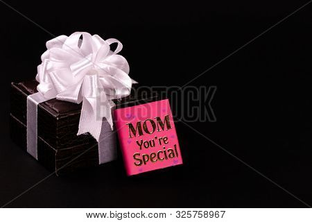 Mother's Day Gift Concept. Brown Leather Gift Box Decorated With White Ribbon And Mom You're Special