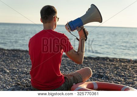 Beach lifeguard with megaphone on duty. Lifeguard on duty seen from behind. The concept of water safety. life buoy on the beach poster