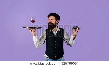 Handsome Man Waiter In Uniform At Restaurant. Waiter Holds Tray With Wine And Metal Cloche Lid Cover