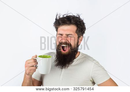 Yawning Man With Sleepy Face Try To Awake With Cup Of Coffee. Man Hold Mug With Hot Drink. Man With