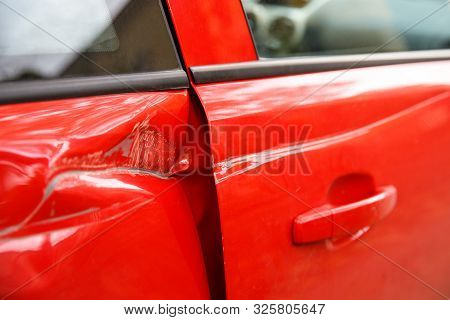 Door Red Car Damaged In A Deep Dent Accident, Scratches On The Doors. Car Repair Concept.