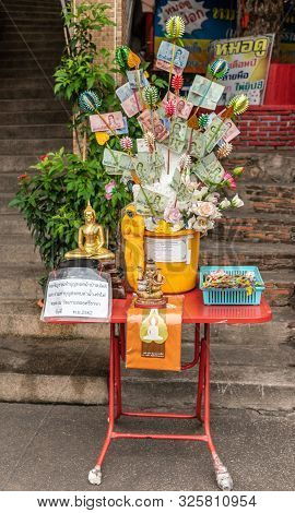 Si Racha, Thailand - March 16, 2019: Yellow Donation Box Vase With Small Statues Set On Red Table At