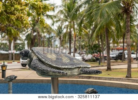 Si Racha, Thailand - March 16, 2019: Bronze Statue Of Turtle On Pole Above Blue Water Pond On Ko Loi