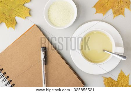 Top view of green tea matcha in a white mug,near notebook for notes on a gray background with maple leaves. Matcha ginger latte. Concept - healthy autumn drinks. Copy space for text poster