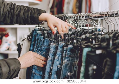 Fast Fashion Concept. Woman Chooses Jeans In A Store. Lots Of Clothes In The Store. Fast Fashion Des