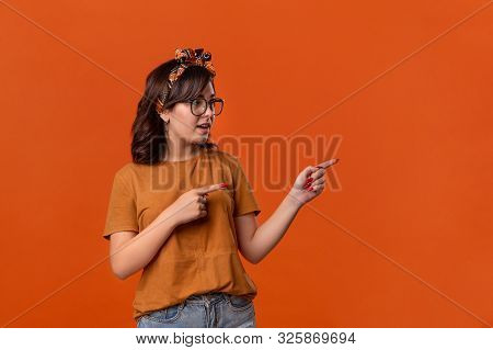 Smiling Brunette Woman In A T-shirt, Beautiful Headband And Eyeglasses Pointing With Her Fingers At