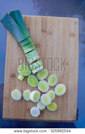 Organic Fresh Cutted Leeks On The Wooden Cutting Board. Leek Cut By Means Rings On A Chopping Board.