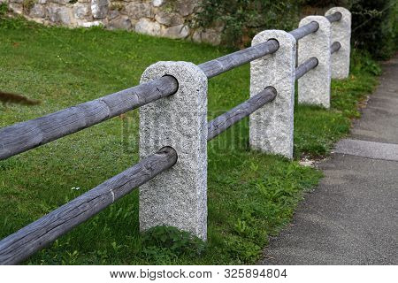 Fence Of Stone Columns And Wooden Bars