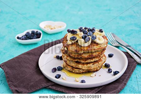 Banana Oat Pancakes With Hazelnuts, Sliced Banana, Honey And Honeysuckle On A White Plate On A Turqu