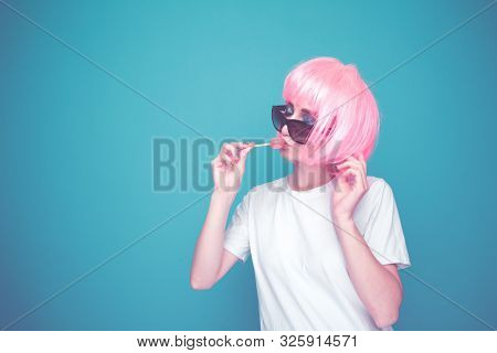 Bautiful 90s Girl In A Whit T-shurt And Black Glasses With Lollipop In A Blue Room.