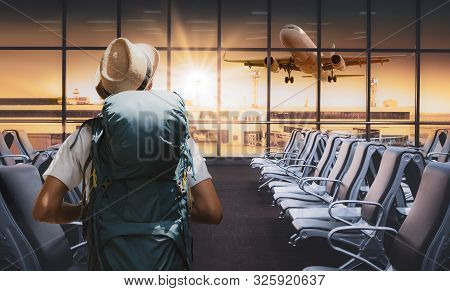 Travel Tourist Standing With Backpack Watching Sunset At Airport Window. Passenger Seat In Departure