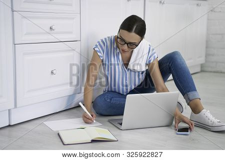 Busy Woman Writing And Taking Smartphone Stock Photo