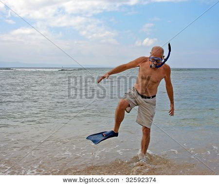 Man with snorkel gear at beach