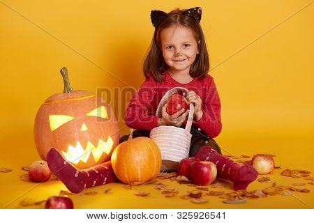 Portrait Of Little Girl In Costume Of Cat, Kid Sitting On Floor With Trick Or Treat Basket, Surround