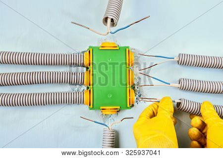 Electric Services, Electrician Connects The Electrical Conduit To A Rectangular Plastic Distribution