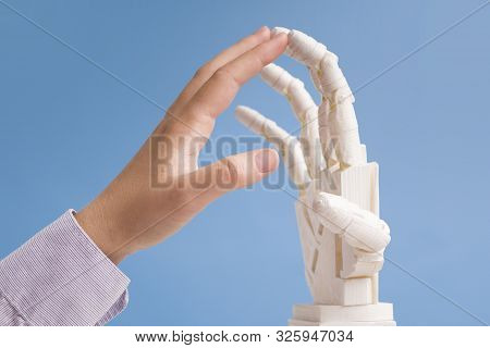 Real And Artificial Feelings. Human And Robot Hands Touching Each Other, Blue Background