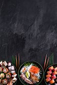Assorted sushi set on dark slate background. Sushi maki roll with salmon, scallop, eel and prawn sashimi served with daikon radish. Copy space for text. Restaurant menu. Traditional japanese food. poster