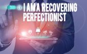 Text sign showing I Am A Recovering Perfectionist. Conceptual photo Obsessive compulsive disorder recovery Male human wear formal work suit presenting presentation using smart device. poster