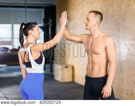 Portrait Of A Sporty Man And Woman: Attractive Fitness Couple Love Giving High Five Together After W