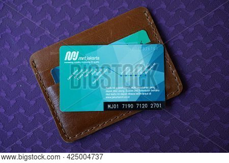Jakarta, Indonesia. June, 26 2021. Multi-trip Card Above Brown Leather Wallet. This Multi-trip Card