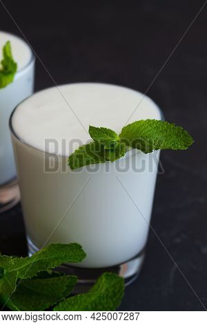 Yogurt With Mint.close-up Lassi Drink With Fresh Green Mint On Black. Cold Dairy. Indian Cuisine. Co