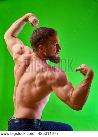 Bodybuilder Posing. Young Athlete And Muscular Athlete Shows Shape. Caucasian Man With A Beard On A