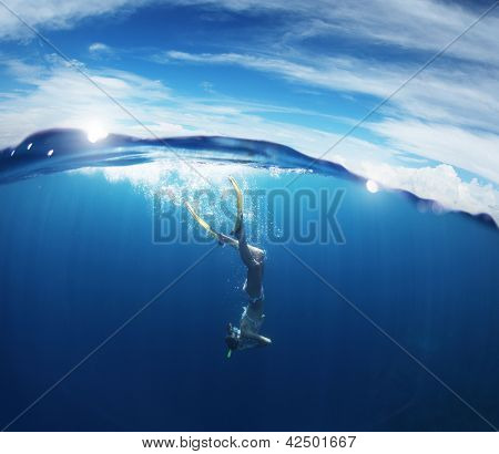 Young lady snorkeling and diving on a breath hold in a clear tropical sea with blue sky with sun and clouds on a surface